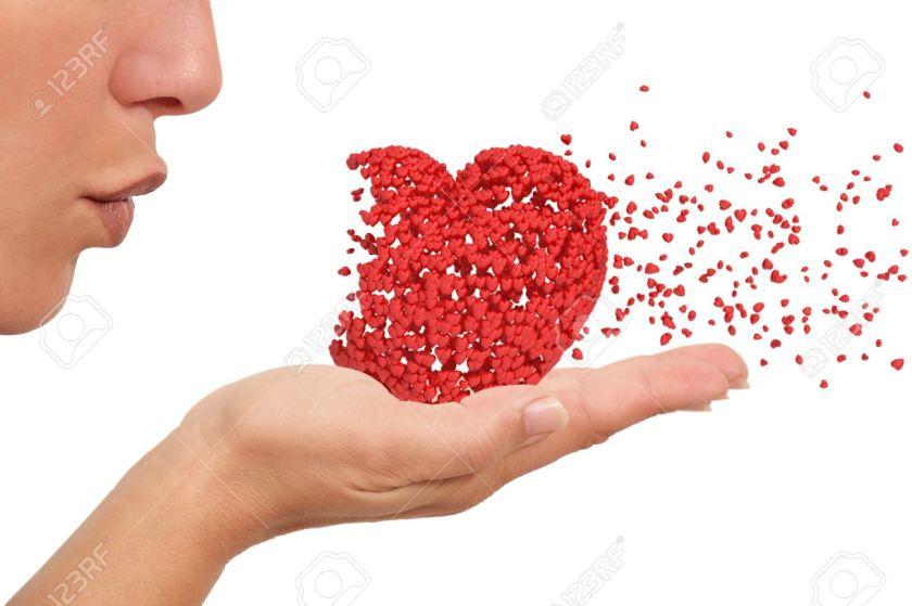 16393012-mujer-que-sopla-un-coraz-n-hecho-de-peque-os-corazones-que-sostiene-en-su-mano-desintegrating-sobre-foto-de-archivo
